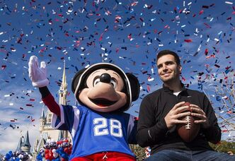In this photo provided by Disney, Super Bowl MVP Joe Flacco rides with the character Mickey Mouse in a parade through the Magic Kingdom at Walt Disney World Resort on Monday, Feb. 4, 2013, in Lake Buena Vista, Fla. Baltimore Ravens quarterback Joe Flacco led his team to a 34-31 victory over the San Francisco 49ers at the NFL Super Bowl XLVII football game on Sunday in New Orleans. (AP Photo/Disney, Matt Stroshane)