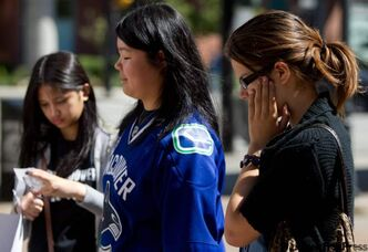 People pause at a makeshift memorial for former Vancouver Canucks hockey player Rick Rypien outside Rogers Arena in Vancouver, B.C., on Tuesday August 16, 2011. Rypien, who signed a one-year deal with the Winnipeg Jets in July, was found dead at his Alberta home on Monday. THE CANADIAN PRESS/Darryl Dyck