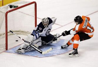 Winnipeg Jets goaltender Ondrej Pavelec deflects a shot from Philadelphia Flyers' Sean Couturier during the shootout period of their NHL game Tuesday in Philadelphia. The Jets won 2-1.
