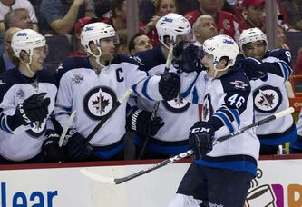 The Winnipeg Jets' Spencer Machacek (46) is congratulated by teammates after scoring during a March 23, 2012 game against the Washington Capitals.