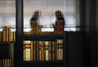 People are reflected in the windows of the British Library where old books are kept in London, Wednesday, April 3, 2013. Capturing the unruly, ever-changing Internet is like trying to pin down a raging river. But the British Library is going to try. For centuries the library has preserved a copy of every book, pamphlet, magazine and newspaper published in Britain. Starting Saturday, April 6, 2013, it will also be bound to record every website, e-book and blog, in a bid to preserve the nation's
