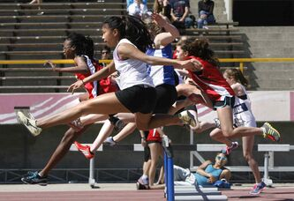 In foregound, Jessica Panesa from Sisler High School runs with the pack over the first hurdle in the senior girls 80m heats at the 2014 Milk Provincial High School Track & Field Championship at the U of M University Stadium Friday. The championship runs until June 7.