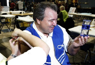 David Chartrand, president of the Manitoba Métis Federation, comforts three-year-old grandson, Isiah, as he gets vaccinated.