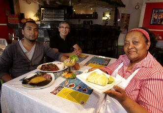 Maria Victoria Zamora (right) and her husband Guillermo Caceres (centre) with son Jonathan Caceres (left) at La Rica Vicky with a few of their famous dishes, including the empanada, which Maria is holding.