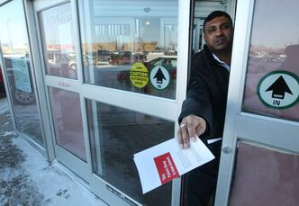 A security guard at the Future Shop on Regent Avenue hands a pamphlet out the front door indicating that the store is now closed.