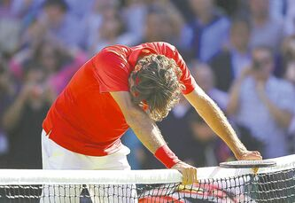 Robert Gauthier / Los Angeles Times / MCTAn exhausted Roger Federer leans on the net after beating Juan Martin Del Potro.