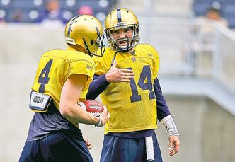 Quarterbacks Buck Pierce (left) and Chase Clement chat at camp.