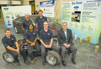Formula SAE Electric members (from left): Kevin Lamothe, Nishant Balakrishnan and Matthew Riesmeyer beside Ford Motor Co.'s Gilbert Portalatin, chief engineer for the  company's electrified powertrain programs and integration. In back are engineering faculty adviser Ed Hohenberg (left) and Formula Electric team member Graeme Smith.