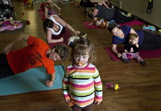 Two-year-old Marena Ewanowich stands amongst exercisers during a Fit Mommy exercise class on Thursday, May 3, 2012 in Edmonton, Alta. More Canadians, it seems, are changing dirty diapers, serving up spoonfuls of mushy peas and getting tongue-tied over Dr. Seuss books before bed, if the latest census figures from Statistics Canada are any indication. THE CANADIAN PRESS/Jason Franson
