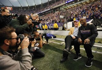 Former Minnesota Vikings coach Bud Grant and current Vikings Adrian Peterson share some time on the bench in Minneapolis in 2013.