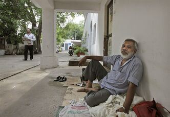 In this Wednesday, July 3, 2013 photo, Jagdish Chand Sharma sits outside the Kashmere Gate telegraph office in New Delhi, India. For nearly 35 years Sharma has made a living helping illiterate customers write telegrams from his mat in a dusty corner of the office's patio. On Monday, July 15, 2013, the state-run telecommunications company will send its final telegram, closing down a service that fast became a relic in an age of email, reliable land lines and ubiquitous cellphones. (AP Photo/Manish Swarup)