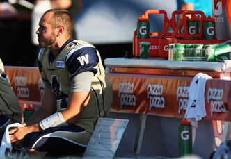 Winnipeg Blue Bombers quarterback Buck Pierce sits on the team bench during first half CFL action as the Hamilton Tiger-Cats take on the Blue Bombers in Guelph, Ont., Saturday.