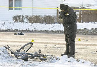 A Winnipeg Police Service forensics officer takes photographs of a bicycle involved in a motor vehicle collision at the corner of Brewster Street and Regent Avenue Sunday morning. The cyclist died of his injuries after being hit by a vehicle driven by an alleged drunk driver.