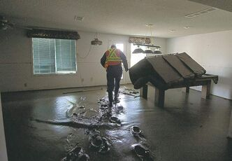 An inspector walks thru muck inspecting a flooded home in High River Friday.
