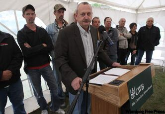Allen Oberg, chair of the Canadian Wheat Board, is surrounded by farmers and friends of the CWB at a news conference at a small farm Monday. The CWB released information today that 60 per cent of prairie wheat growers want to keep the Canadian Wheat Board as the sole marketing agent for their grain, a CWB plebsicite has found.