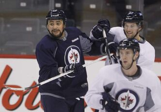 Winnipeg Jets defenceman Dustin Byfuglien (left) tangles with Eric Tangradi during the optional practice at the MTS Centre Wednesday.