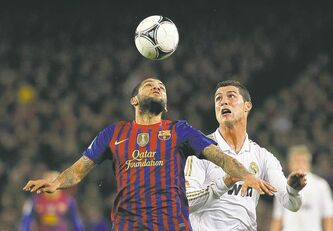 FC Barcelona's Daniel Alves (left) vies for the ball with Real Madrid's Cristiano Ronaldo in a match earlier this season.
