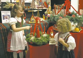 Lianne Konziela lights a candle as her sister Kaitlyn watches during opening of Christkindlmarkt.