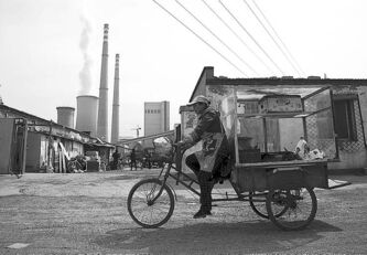 A vendor rides his tricycle near a coal-fired power plant in Beijing on April 12.