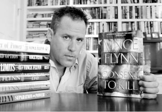In 2005, bestselling author Vince Flynn shows the dust jacket of his latest book beside a stack of six others.
