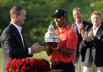 Tiger Woods, center, receives the trophy from Rob Forsyth, AT&T Mobility vice president and general manager, after winning the AT&T National golf tournament at Congressional Country Club in Bethesda, Md., Sunday, July 1, 2012.