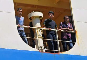 Iraqi asylum seekers look out from a cargo ship that rescued them after their boat sank off Java island while on their way to Australia in July.