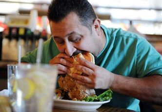 """In htis Wednesday, Jan. 4, 2012 photo, David Romero tries his first Schweinefilet sandwich at the Gerst Haus in Evansville, Ind. The Indiana Office of Tourism has selected 46 sandwiches that will compete in a bracket for best sandwich in the state. The pork tenderloin sandwich is breaded and fried. The Gerst Haus' Schweinefilet sandwich has been chosen to compete with 45 others in a sandwich contest put on by the Indiana Office of Tourism Development, in partnership with the Indianapolis Super Bowl Host Committee and Indianapolis Monthly, to commemorate Super Bowl XLVI in Indianapolis. The list of """"Super 46 Sandwiches"""" was released on Wednesday by the Indiana Office of Tourism Development. While most of the other sandwiches come from Indianapolis eateries, the Schweinefilet from Evansville and the bratwurst from the Schnitzelbank in Jasper, Ind. are on the list from southern Indiana. (AP Photo/The Evansville Courier & Press, Molly Bartels)"""