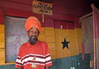 In this Nov. 19, 2012 photo, Rastafarian Priest Noah poses for a photo on the porch of a