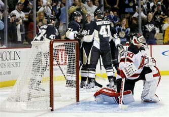 Pittsburgh Penguins players celebrate after' Brandon Sutter scored past New Jersey Devils goalie Martin Brodeur (30) in the second period of an NHL hockey game on Saturday, Feb. 2, 2013 in Pittsburgh. (AP Photo/Keith Srakocic)