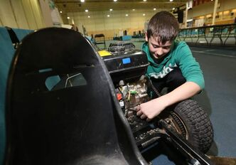 Grade 7 Linden Christian School student Jackson Pankratz, 12, makes some adjustments to his award-winning go-kart Manitoba Science Symposium project.