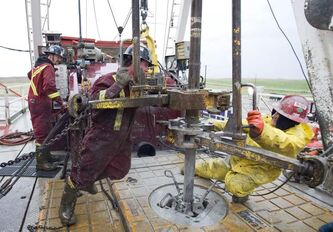 A crew works on the floor of a drilling rig on an oil well near Weyburn, Sask.