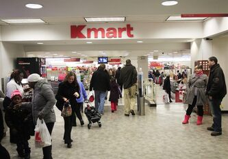 Shoppers leave a Kmart location Tuesday, Dec. 27, 2011, in New York. Sears Holdings Corporation, the parent company of Sears and Kmart department stores, announced Tuesday morning that it will close 100 to 120 stores after a sluggish holiday season.(AP Photo/Frank Franklin II)