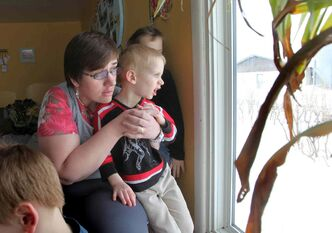 Eveline Wiebe looks out her living room window with her son Larry, two years old, where she could see flames in the middle of the night after natural gas explosion near their home in Otterburne.