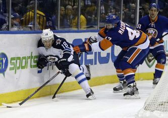 New York Islanders defenceman Andrew MacDonald tries to prevent Winnipeg Jets centre Bryan Little from getting to the puck during an NHL game at Nassau Coliseum in Uniondale, N.Y., Tuesday. The Islanders won 5-2.