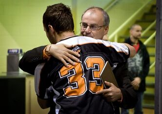 Grand Prairie Composite High School Warriors coach and school principal Rick Gilson, right hugs player Keenan Wood, following a public memorial service in Grand Prairie, Alta., Sunday, Oct. 30, 2011. Four players from the Warriors were killed in a car crash near the town last weekend, and a fifth remains in hospital with head injuries.THE CANADIAN PRESS/Jeff McIntosh