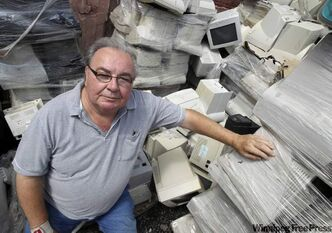 Tom Syrota, owner of Syrotech Indus­tries, in his company's yard piled high with electronic waste.