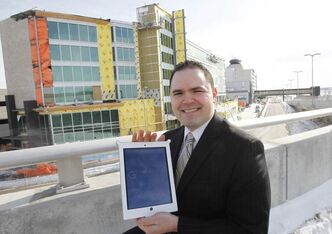 The Grand general manager Neil Fishman holds an iPad. The devices will be available for guests to access services in the new hotel (under construction behind him).