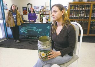 Store owner Angel Calvo hold a donation jar that does double duty collecting water dripping through the roof. Town's residents have until January 2015 to leave; she's been told to close up after summer.