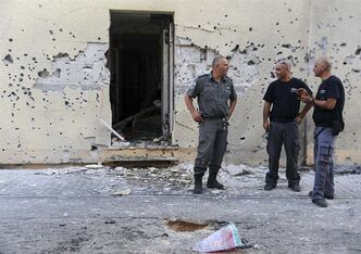 Israeli policemen stand in front of a house damaged by a rocket fired from Lebanon in Shavei Tzion outside Nahariya in northern Israel, Thursday, Aug. 22, 2013. Military spokesman Lt. Col. Peter Lerner said Thursday that three rockets landed in northern Israel, while one was shot down. (AP Photo/Jinipix) ISRAEL OUT