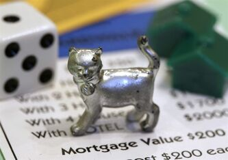 In this Tuesday, Feb. 5, 2013, photo, the newest Monopoly token, a cat, rests on a Boardwalk deed next to a die and houses at Hasbro Inc. headquarters, in Pawtucket, R.I. Hasbro Inc. reports quarterly financial results before the market opens on Monday, April 22, 2013.(AP Photo/Steven Senne)