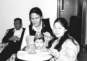 A 20-something Eric Robinson (centre) celebrates his daughter's first birthday with his father and wife.