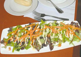 Experts suggest eating a salad before ordering a full meal will help control cravings when traveling.