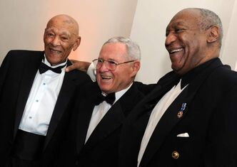 Lanier Phillips (left) was honoured with the U.S. Navy Memorial's Lone Sailor award in 2010. With him was former NFL star Eddie LeBaron and comedian Bill Cosby.