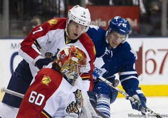 Florida Panthers goalie Jose Theodore (60) makes a save as Panthers defenceman Dmitry Kulikov, centre, and Toronto Maple Leafs forward Nikolai Kulemin, right, battle for puck  in Toronto on Tuesday. The  Panthers won 5-1.