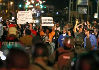 This photo by David Carson shows a line of protestors facing off with police Monday, Aug. 18, 2014, in Ferguson, Mo.