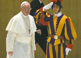 Pope Francis I walks past a Swiss guard as he arrives for a meeting with the media at the Pope VI hall, at the Vatican.