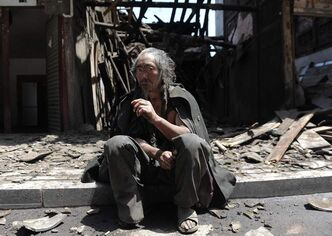A man sits in front of the houses destroyed by the earthquake.