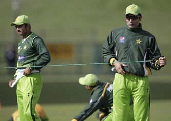 Pakistan's captain Misbah-ul-Haq, right, warms up as his teammate Aizaz Cheema, left, looks on during a cricket practice session at the Sheikh Zayed Cricket Stadium in Abu Dhabi, United Arab Emirates, Tuesday, Jan. 24, 2012. Pakistan are due to play England in their second cricket test match in starting Abu Dhabi on Wednesday. (AP Photo/Hassan Ammar)