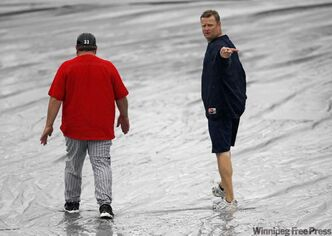 Goldeyes manager Rick Forney (right) inspects Canwest Park's field with Fargo manager Doug Simunic before Saturday's game was postponed due to rain.