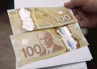 The Bank of Canada's new circulating $100 bill, Canada's first polymer bank note, is shown in Toronto on Monday Nov. 14, 2011. The Bank of Canada considered celebrating gay marriages, black hockey players, and turban-wearing RCMP officers on its new plastic bank notes, but eventually nixed them all in favour of the more traditional images of a train, a ship and a monument.